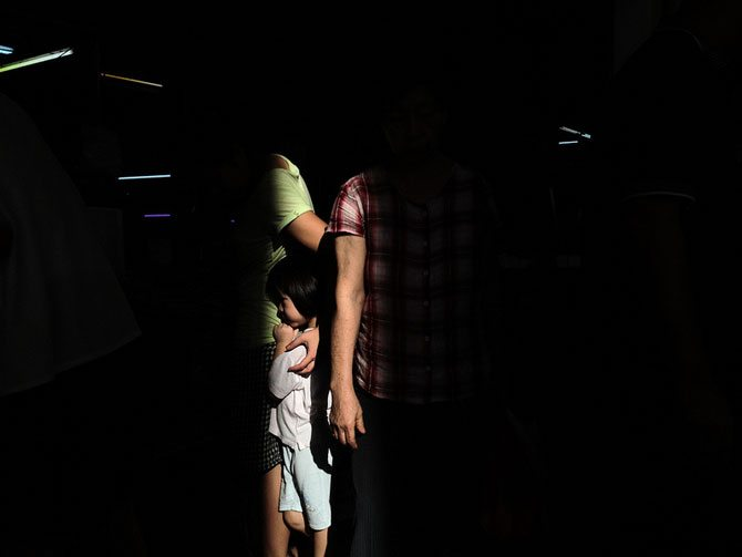 Light Through Darkness A Mothers Love Featured Street Photographer: AikBeng Chia from the Mobile Photo Group